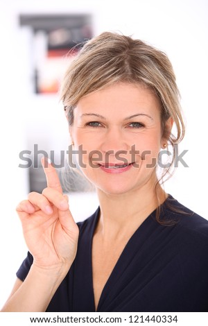 Beautiful mid aged blonde with cream on a finger smiling - stock photo