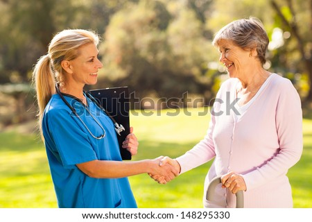 beautiful mid aged nurse handshaking senior patient outdoors - stock photo