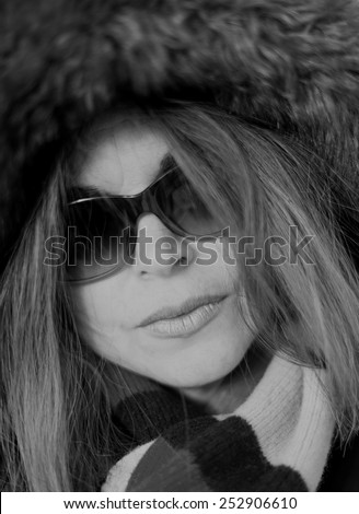 Beautiful middle age woman close up portrait wearing a thick coat in the Canadian Winter. Creative shallow depth of field to enhance lips - stock photo