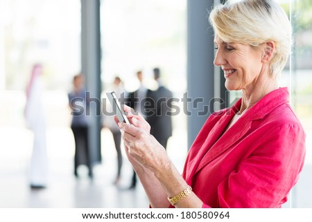 beautiful middle aged businesswoman reading email on smart phone - stock photo