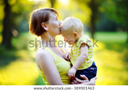 Beautiful middle aged woman and her adorable little grandson at sunny park