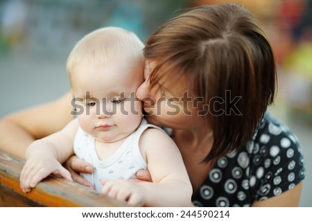 Beautiful middle aged woman and her adorable little grandson at the summer park  - stock photo