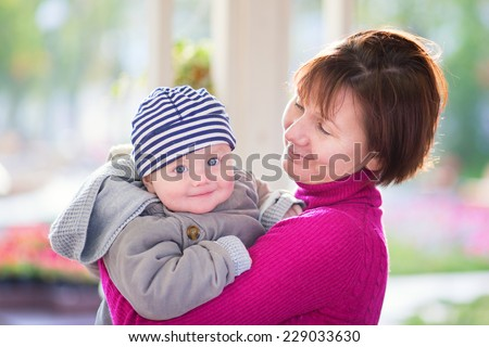 Beautiful middle aged woman and her adorable little grandson having fun together in an outdoor cafe on a fall or spring day - stock photo