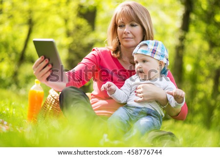 Beautiful middle aged woman and her adorable little son having a picnic in sunny park - stock photo