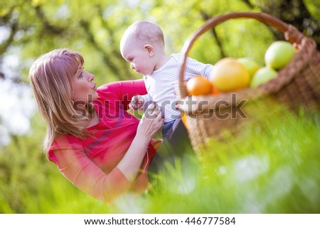 Beautiful middle aged woman and her adorable little son having a picnic in the park. - stock photo