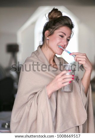 Beautiful middle-aged woman brushes her teeth and maintains mouth hygiene in the living room with a daylight