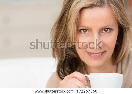 Beautiful middle-aged woman drinking a relaxing cup of tea or coffee smiling over the rim at the camera, with copyspace