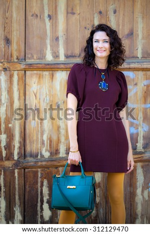 beautiful middle-aged woman in a burgundy dress and green handbag near aged doors - stock photo