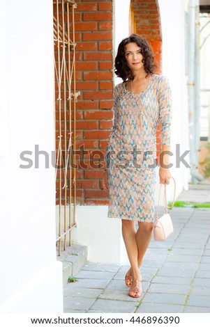 beautiful middle-aged woman in a summer dress in a hand bag near the vintage gate - stock photo