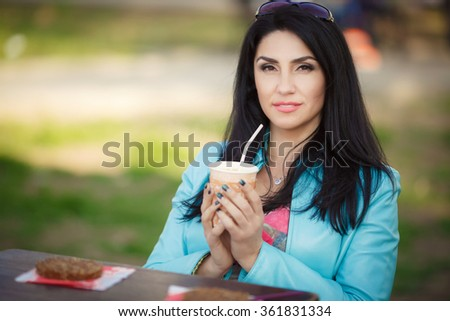 Beautiful middle aged woman in cafe outdoors, smiling woman drinking coffee at street cafe, happy middle age woman portrait, soft grain instagram filter like, series - stock photo