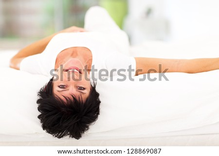 beautiful middle aged woman lying on bed at home
