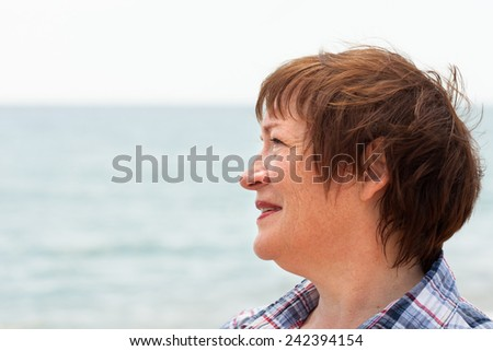 beautiful middle-aged woman on  beach near  sea.  - stock photo