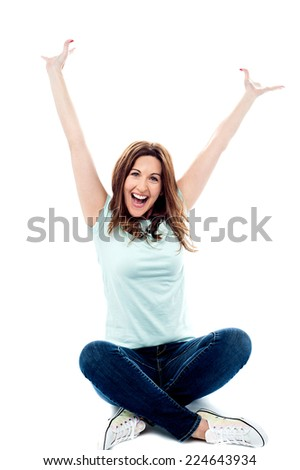 Beautiful middle aged woman sitting with arms raised - stock photo