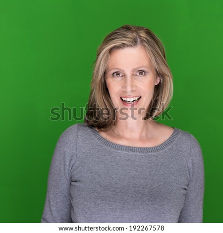 Beautiful middle-aged woman with a lovely smile standing against a green background with copyspace looking at the camera - stock photo