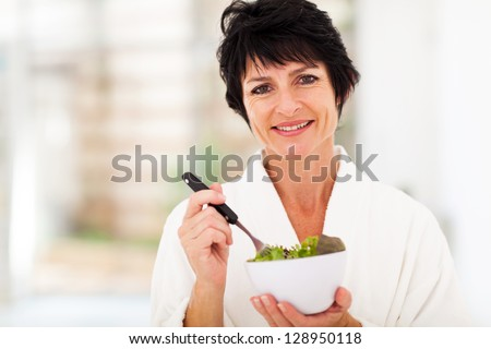beautiful middle aged woman with healthy salad at home