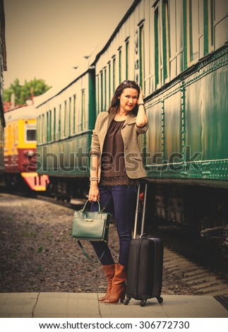 beautiful middle-aged woman with luggage near the old train. retro trip. instagram image filter retro style - stock photo