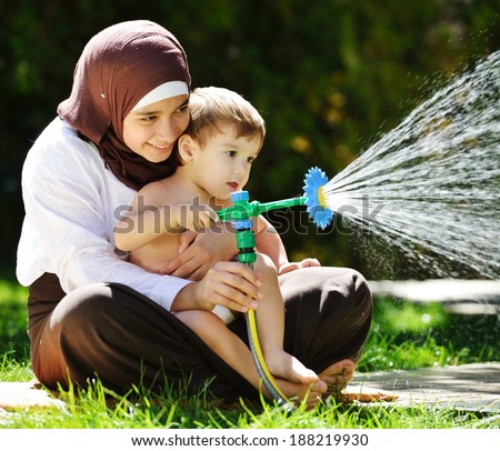 Beautiful Middle Eastern Arabic girl having baby playing with water sprinkler in garden - stock photo
