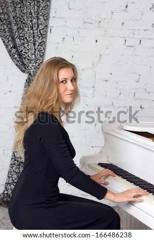 Beautiful middle eastern girl playing piano - stock photo