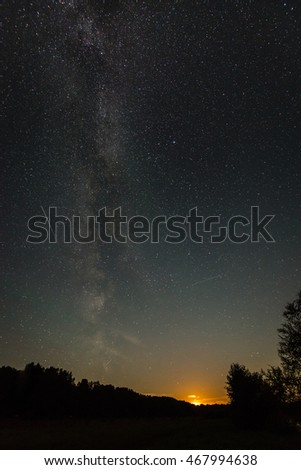 Beautiful milky way galaxy on a night sky and silhouette of tree with cloud, Long exposure photograph.with grain