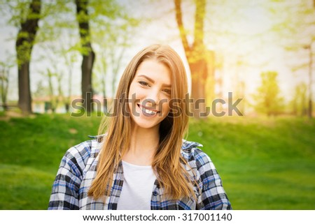 Beautiful millennial teenage girl in park in autumn smiling. Portrait of cute young woman in blue plaid shirt outdoors on sunny day. Retouched, vibrant colors, horizontal. - stock photo