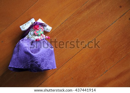 Beautiful miniature version of Korean wedding dress on wooden background