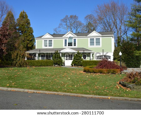 Beautiful Mint Green Suburban McMansion Home clear blue sky autumn day residential neighborhood USA - stock photo