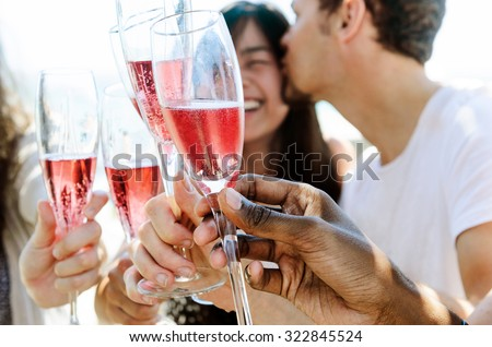 Beautiful mix race couple celebrating their engagement with champagne and their friends on the beach - stock photo