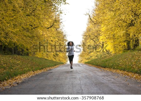 Beautiful mixed race African American young woman girl teenager fitness running jogging in Autumn Fall trees - stock photo