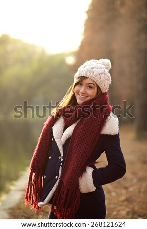 Beautiful mixed race girl smiling in a park in Winter clothes with sunset - stock photo