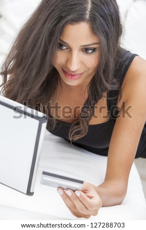 Beautiful mixed race Hispanic Latina woman using a credit card to shop on line using the internet and a tablet computer