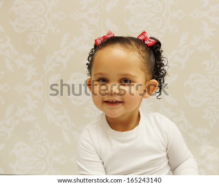 Beautiful mixed race toddler posing in studio setting, happy smiling face. - stock photo
