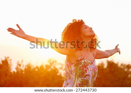 Beautiful mixed race woman expressing freedom on a summer evening outdoors with her arms outstretched - stock photo