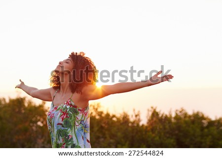 Beautiful mixed race woman expressing freedom outdoors with her arms outstretched - stock photo
