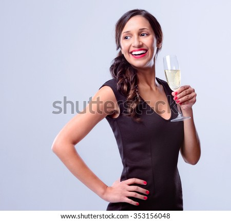 Beautiful mixed race woman holding a glass of champagne looking away, wearing a little black dress for new years eve party celebration