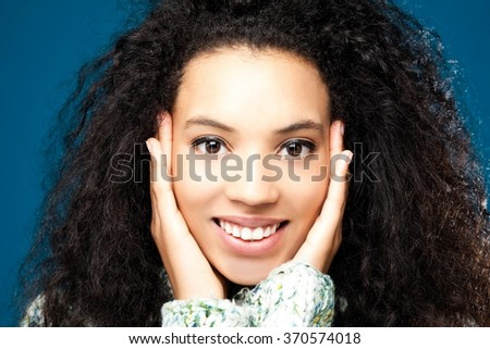 Beautiful mixed race woman holding hands on her face - close up.