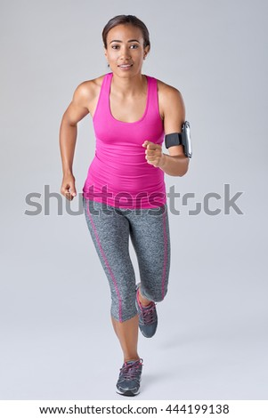 Beautiful mixed race woman running in studio, with wearable technology sports exercise apps - stock photo