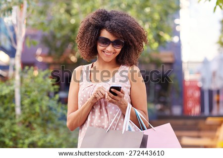 Beautiful mixed race woman smiling while using her phone and standing outdoors with shopping bags over her arm  - stock photo