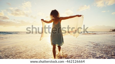 Beautiful mixed race young woman walking on beach at sunset