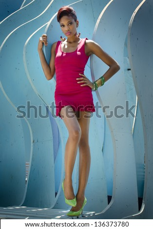 Beautiful model actress wearing short dress against blue background.