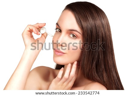 Beautiful model applying a cosmetic skin serum treatment on white - stock photo