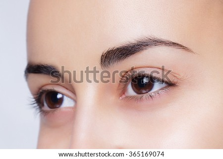 beautiful model applying cosmetic cream treatment on her face on white - stock photo