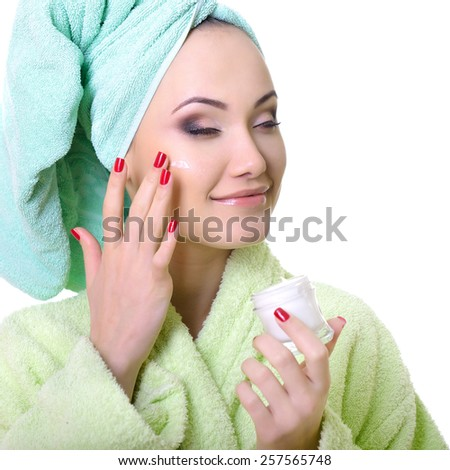beautiful model applying cosmetic cream treatment on her face, over white background - stock photo