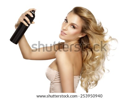 beautiful model applying spray  on windy hair on white - stock photo