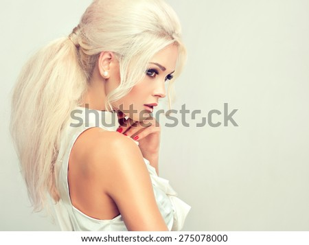 Beautiful model blonde with retro hair , bouffant hair, and a bushy tail . Red nails manicure and white blouse  - stock photo