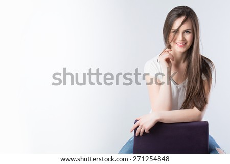 Beautiful model brunette with long hair sitting and smiling. - stock photo