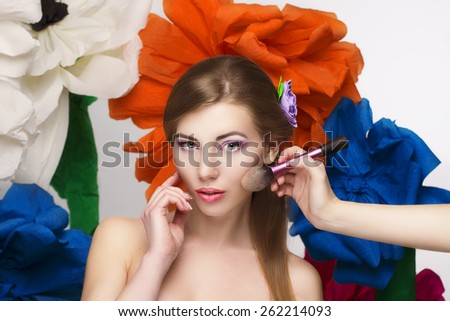 Beautiful model girl doing a make up brush paint