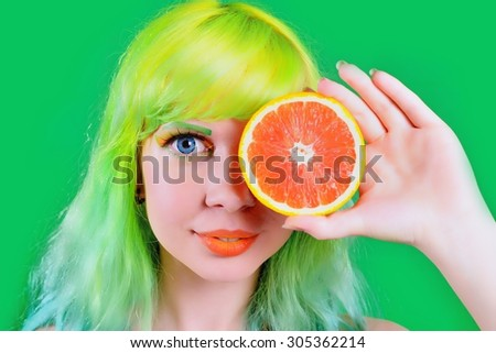Beautiful model girl with colorful hairstyle takes red juice on green background