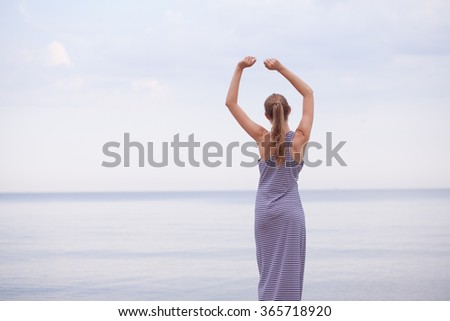 Beautiful model girl with long blond hair stands on the shore of the beach on the sunset in long wonderful summer dress and looks at the blue clear sea