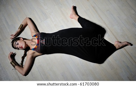 Beautiful model girl with long hair and bright make-up on the wooden floor - stock photo