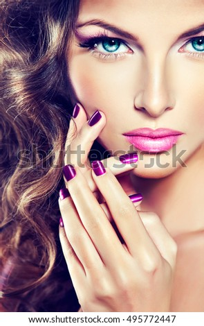 Beautiful model girl with long wavy and shiny hair . Brunette woman with curly hairstyle  and purple manicure